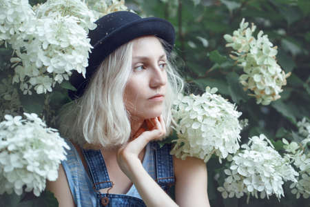 platinum: Closeup portrait of beautiful Caucasian teenage young blonde alternative model girl woman in blue tshirt, jeans romper, black hat, sitting among large white flowers on summer day