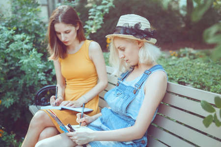 Portrait of two white Caucasian young girls hipster students friends outside in park on summer day sitting on bench together, drawing, sketching, best friends forever, toned with filters Stock Photo