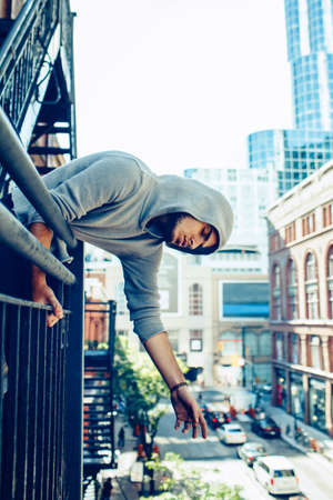infernal: Conceptual art portrait of beautiful handsome pensive sad tired gothic young middle east brunette man with beard in hoodie, standing on staircase in city urban looking down on street