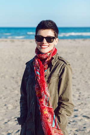 Portret van gelukkig lachend mooie blanke wit brunette vrouw met kort haar in groene jas, rode sjaal en een zonnebril, kijkend in de camera, staande op zee oceaan strand bij zonsondergang
