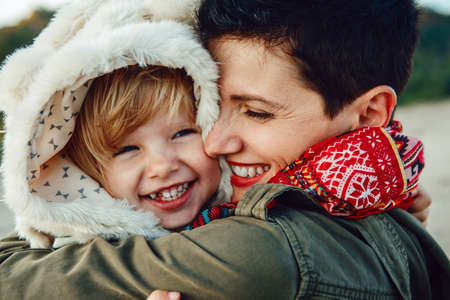 winter: Closeup group portrait of white Caucasian mother and daughter baby girl hugging smiling laughing on sunset, autumn fall winter season, happy lifestyle childhood concept Stock Photo