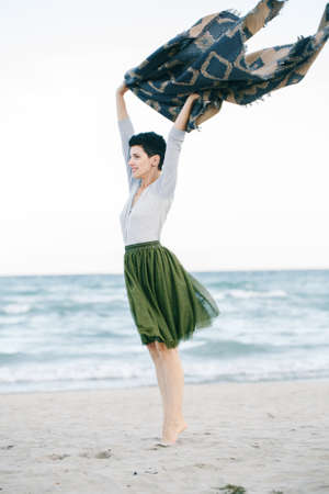 아름 다운 백인 백색 갈색 머리 여자 녹색 올리브 투투 얇은 명주 그물 치마에 짧은 머리와 함께 큰 목도리 스카프, 맨발로 발끝에 멀리 찾고 해변에 서있는의 초상화
