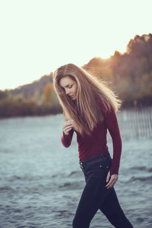 cinematic: portrait of young Caucasian slim woman with messy long hair wearing black jeans and red shirt walking on windy autumn day outdoor on beach, motion action blur, hipster film effect style Stock Photo