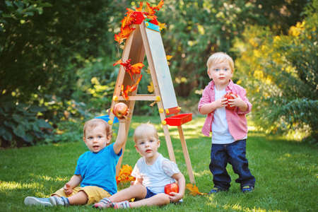 Group of three white Caucasian toddler children kids boys and girl outside in summer autumn park by drawing easel holding apples Stock Photo