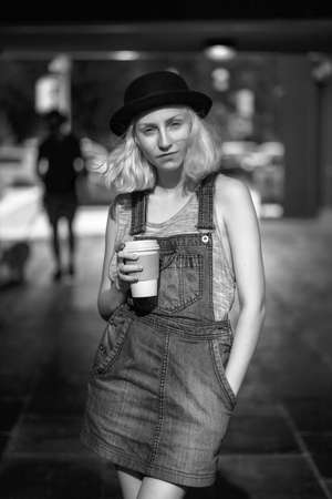 romper: Black and white portrait of Caucasian teenage young blonde alternative model girl woman in tshirt, jeans romper looking in camera holding cup of coffee