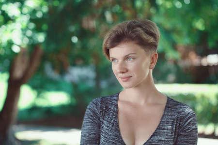 Portret van lachende jonge middelbare leeftijd blanke blanke meisje vrouw met kort haar stijlvolle kapsel in t-shirt weg te kijken buiten in de zomer park