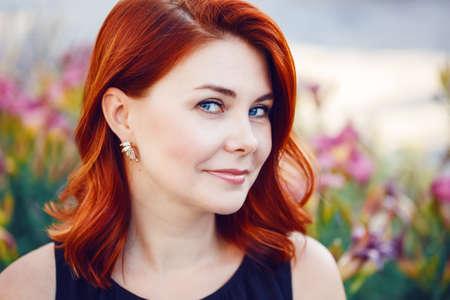 중간 미소의 근접 촬영 초상화 꽃으로 가운데 공원에서 카메라를 찾고 검은 드레스에 흔들며 곱슬 빨간 머리를 가진 백인 백인 여자 세