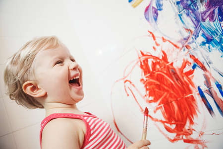 bathroom wall: Portrait of cute adorable white Caucasian little boy girl playing and painting with paints on wall in bathroom having fun