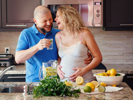 cravings: Portrait of smiling laughing white Caucasian couple two people pregnant woman with husband cooking food, drinking citrus juice in kitchen