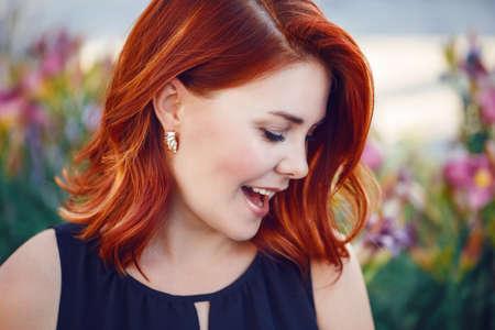 Retrato de la sonrisa de risa mujer blanca de mediana edad coqueta caucásico con el pelo rojo rizado ondulado en traje negro gritando fuera en el parque