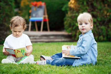Group of two white Caucasian toddler children kids boy and girl sitting outside in grass in summer autumn park by drawing easel with books