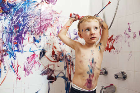 mess: Portrait of cute adorable white Caucasian little boy playing and painting with paints on wall in bathroom having fun