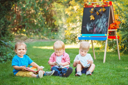 Group of three white Caucasian toddler children kids boys and girl sitting outside in summer autumn park by drawing easel with books