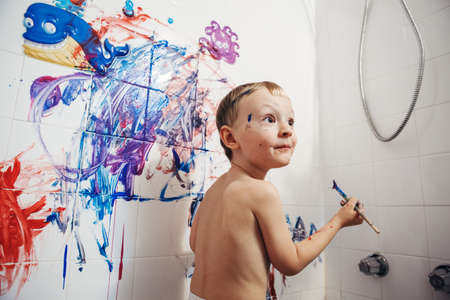 bathroom wall: Portrait of cute adorable white Caucasian little boy playing and painting with paints on wall in bathroom having fun