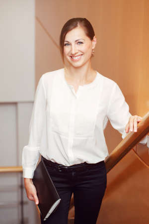 Portrait of beautiful smiling nice young white Caucasian business woman with blue eyes wearing white office blouse shirt and black pants, looking in camera, slavic Russian European face Stock Photo