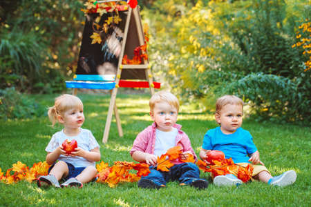 Group of three white Caucasian toddler children kids boys and girl sitting outside in summer autumn park by drawing easel with fall leaves and apple