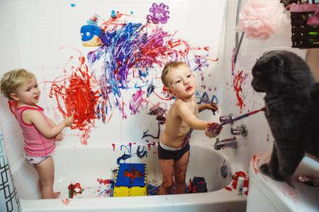 2 つのかわいい愛らしい白い白人の肖像幼い男の子と女の子が遊ぶ楽しい浴室塗料と塗装猫