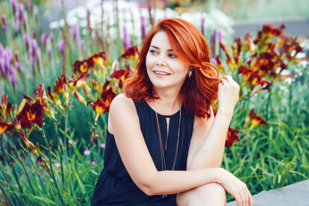 Closeup portrait of smiling middle aged white caucasian woman with waved curly red hair in black dress looking away outside in park garden among flowers Archivio Fotografico