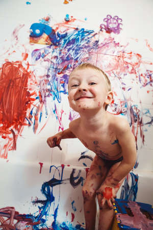 bathroom wall: Portrait of cute adorable white Caucasian little boy playing and painting with paints  on wall in bathroom having fun, lifestyle childhood concept Stock Photo