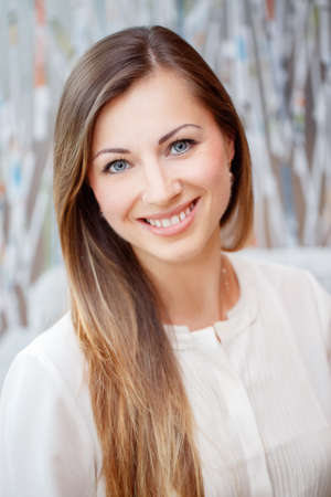 oriented: Closeup portrait of beautiful smiling nice young white Caucasian business woman with blue eyes long blond hair wearing white office blouse shirt Stock Photo