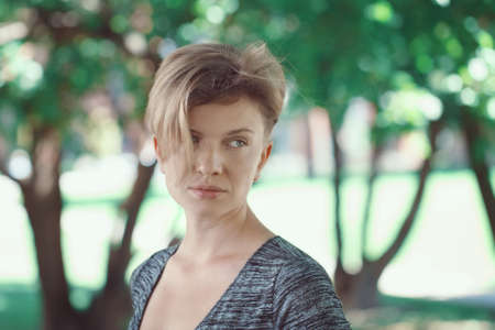 haircut: Closeup portrait of sad upset pensive young middle aged white caucasian girl woman with short hair stylish haircut in t-shirt looking away outside in summer park Stock Photo