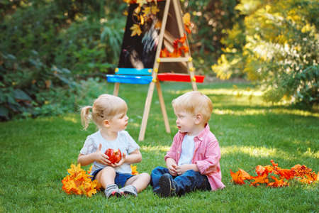Group of two white Caucasian toddler children kids boy and girl sitting outside in summer autumn park by drawing easel looking at each other, playing eating apple