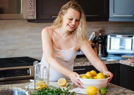 cravings: Portrait of smiling white Caucasian blonde pregnant woman with citrus lime lemon making juice standing in kitchen at home looking away
