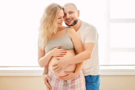 middle age couple: Portrait of smiling laughing white Caucasian young middle age couple, pregnant woman with husband in room hugging cuddling