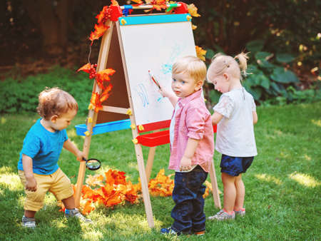 Group of three white Caucasian toddler children kids boys and girl standing outside in summer autumn park by drawing easel with markers