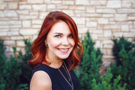 Closeup portrait of smiling middle aged white caucasian woman with waved curly red hair in black dress looking in camera outside in park garden