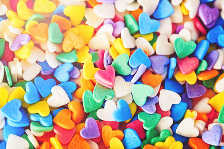 Heap of colorful candies confetti of  heart shape, abstract background, Valentine Day holiday concept, macro photograph, horizontal