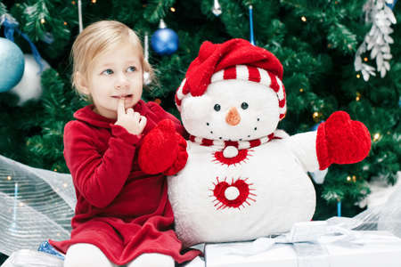 baby near christmas tree: Portrait of happy smiling Caucasian baby girl toddler with blue eyes in red dress sitting  by New Year tree  near snowman toy, emotional lifestyle Christmas holiday concept Stock Photo