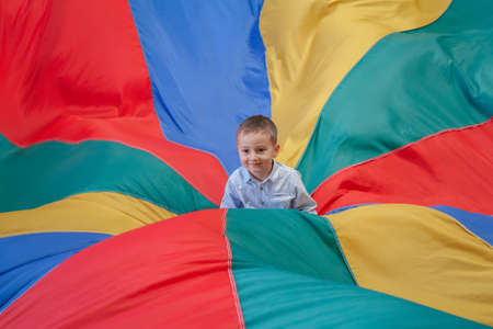 babies playing: Portrait of white Caucasian child boy toddler sitting in the center of playground rainbow parachute celebrating his birthday at party