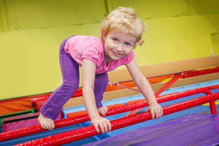 tumbling: Portrait of white blonde Caucasian happy smiling baby girl child doing exercises in gym enjoying sport class