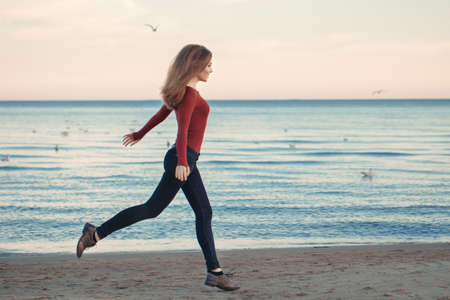 portrait of happy smiling laughing excited Caucasian young woman in jeans running jumping among seagulls birds on autumn fall day outdoor on the shore beach at sunset, lifestyle natural emotion Stock Photo