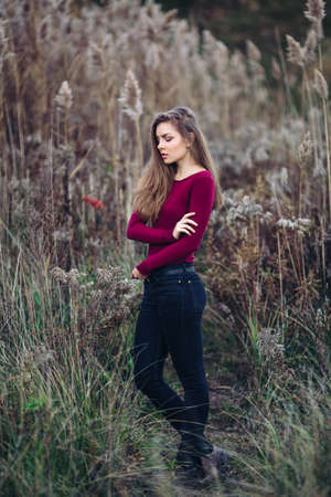 Portrait of pensive sad lonely Caucasian blonde young beautiful woman girl with long hair wearing jeans, red shirt,  in forest field among large tall plants grass, looking away