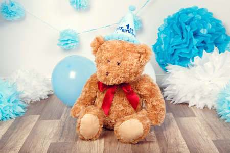 Festive background decoration for first year birthday celebration with little bear toy sitting on floor in studio, balloons, paper flowers and presents gift boxes, toned with filters