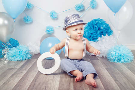 Portrait of cute adorable Caucasian baby boy with blue eyes barefoot  in pants with suspenders and hat, sitting on wooden floor in studio, holding large letter O, looking away, first year concept