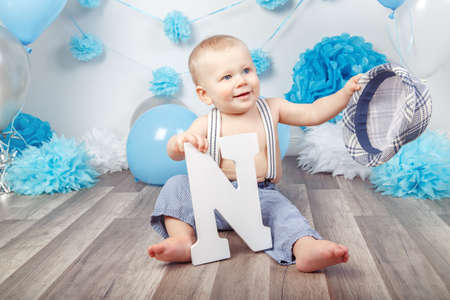 Portrait of cute adorable Caucasian baby boy with blue eyes barefoot  in pants with suspenders and hat, sitting on wooden floor in studio, holding large letter N, looking away, first year concept Stockfoto