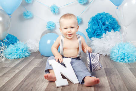 Portrait of cute adorable Caucasian baby boy with blue eyes barefoot in pants with suspenders and hat, sitting on wooden floor in studio, holding large letter N, looking in camera, first year concept
