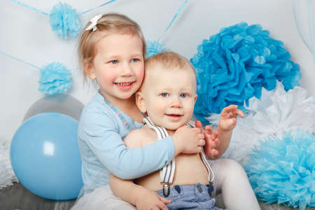 Portrait of two smiling laughing hugging cute adorable Caucasian children, toddler girl and baby boy, celebrating birthday looking in camera, white studio background with blue balloons