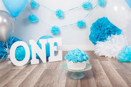 Decorazione festiva del fondo per la celebrazione di compleanno con il dolce gastronomico, lettere che dicono uno e palloni blu in studio, concetto del primo anno della moneta falsa del dolce Archivio Fotografico