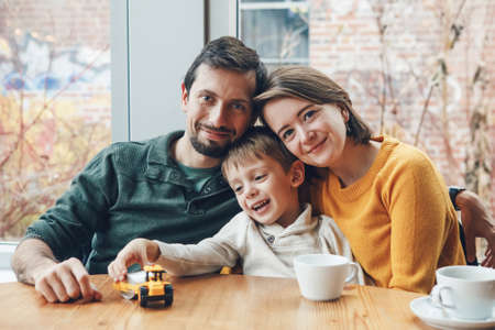 Portrait of white Caucasian happy family of three mother, father and son, sitting in restaurant cafe at table, smiling playing, authentic lifestyle