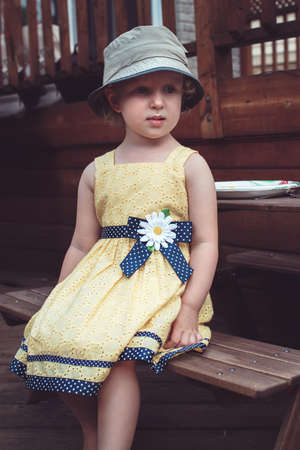 Portrait of cute Caucasian girl in yellow dress and hat  outside on house backyard on summer day, sitting on wooden bench at table with plate waiting for food Foto de archivo