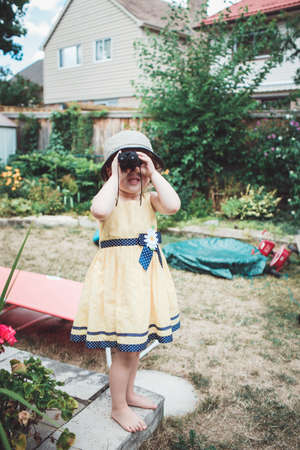 Portrait of cute Caucasian girl in yellow dress and hat  looking through binoculars, outside on house backyard, playing spy game, candid childhood lifestyle