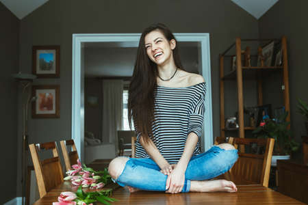Portrait of smiling laughing Caucasian young beautiful woman model with messy long hair in ripped blue jeans and striped t-shirt sitting on table with flowers indoor looking away, toned with filters