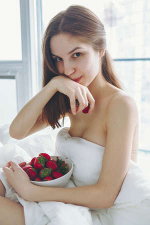 Portrait of smiling beautiful young Caucasian woman with long hair sitting in bed early morning by window, eating red fresh strawberry, wiping her mouth by hand,  lifestyle, toned with filters