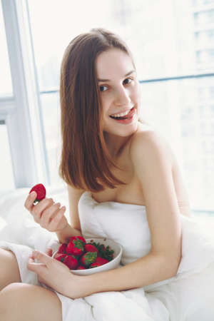 Portrait of smiling beautiful young Caucasian woman with long hair sitting in bed early morning by window, eating red fresh strawberry, showing her tongue flirting, lifestyle, toned with filters Foto de archivo