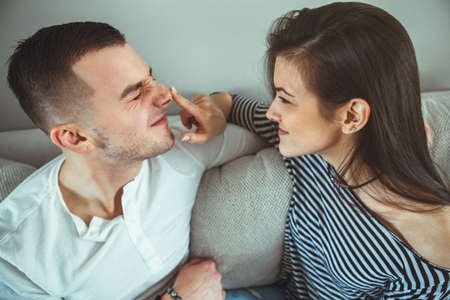 Portrait of beautiful smiling laughing romantic young couple man woman in love  having fun, indoors at home sitting on couch in room, toned with filters, authentic lifestyle