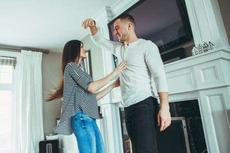 Portrait of beautiful romantic young smiling laughing couple man woman in love hugging, kissing, dancing together indoors at home  in room, toned with filters, authentic candid lifestyle Foto de archivo